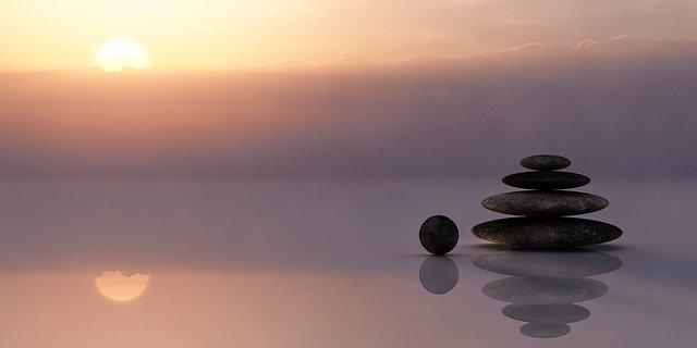 coucher de soleil avec, sur la plage des pierres en équilibre.